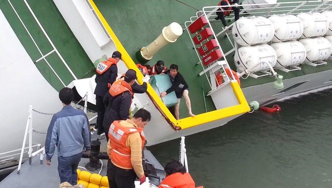 Sewol ferry captain Lee Joon-Seok (C-R), wearing a sweater and underpants, is rescued from the tilting vessel before it sank.