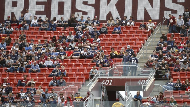 FILE - In this Oct. 6, 2019, file photo, fans watch play between the Washington Redskins and the New England Patriots during the second half of an NFL football game, in Landover, Md. A new name must still be selected for the Washington Redskins football team, one of the oldest and most storied teams in the National Football League, and it was unclear how soon that will happen. But for now, arguably the most polarizing name in North American professional sports is gone at a time of reckoning over racial injustice, iconography and racism in the U.S.