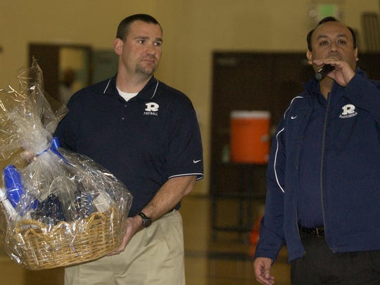 Published in print  Redwood principal Dr. Fernie Marroquin introduces new head football coach Shaun Ball to the crowd during halftime of their basketball game against El Diamante at Redwood High School on Wednesday. Ball received a gift basket from the school.