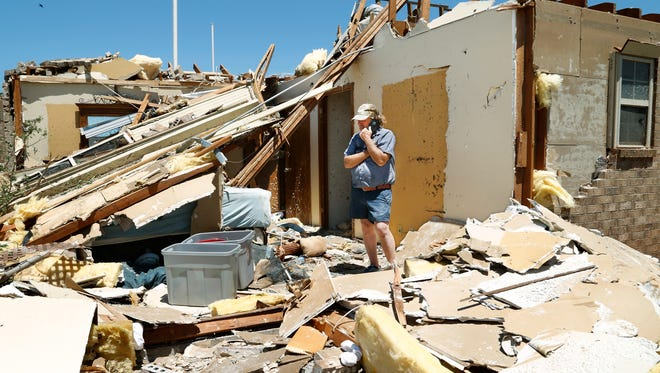 Jody Darling, a friend of the residents of this home in Elk City, Okla., talks on a phone while standing in a room of the house that is now totally exposed on Wednesday, May 17, 2017. Over a dozen tornadoes were reportedly spawned by powerful storms that raced through a swath of the central U.S. stretching from Texas to the Great Lakes on Tuesday evening, killing two people.