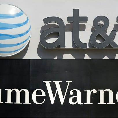 This file combination of pictures created on Oct. 21, 2016, shows an AT&T cellphone store in Springfield, Va., and the Time Warner company logo on the front of the headquarters building in New York.