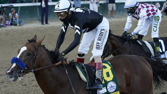 Jockey John Velazquez riding Authentic crosses the finish line ahead of Jockey Manny Franco riding Tiz the Law to win the 146th running of the Kentucky Derby at Churchill Downs on Saturday.