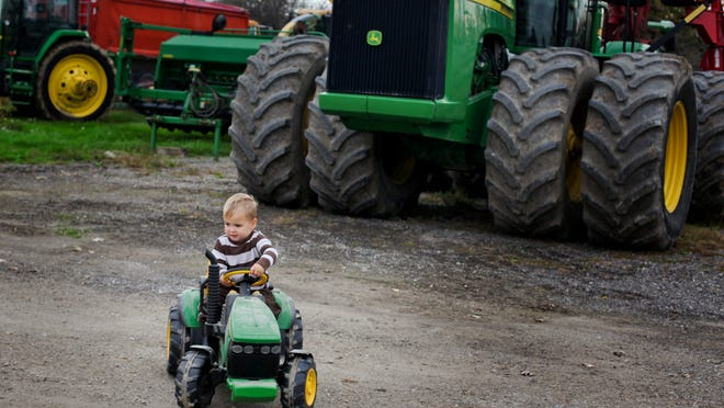 Parker Bauer, 23 months old, rides a small electric John Deere tractor past large farm equipment while visiting Fahley Farms in Emmett Township.