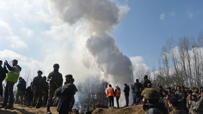 Indian soldiers and Kashmiri onlookers stand near the remains of an Indian Air Force helicopter after it crashed in Budgam district, outside Srinagar on Feb. 27, 2019.