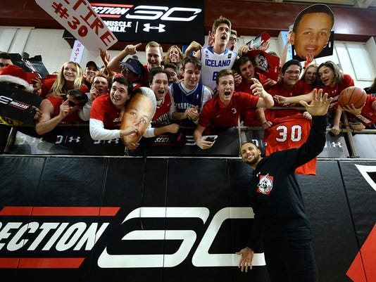 NBA star Stephen Curry, a former basket player for Davidson College, poses with students in front of the newly renamed Section 30 for Curry's uniform number he wore for the Wildcats, while visiting the campus in Davidson, N.C., Tuesday, Jan. 24, 2017. (Jeff Siner/The Charlotte Observer via AP)
