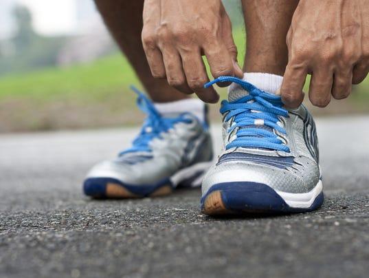 Man bending down tying his sports shoes