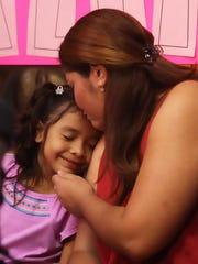 Alison Jimena Valencia Madrid, 6, left, leans in for