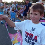 Hayden Crisp tries his hand with a sparkler while waiting with the rest of his family on Bayfront Parkway for the start of a past Sertoma's fireworks display over Pensacola Bay.