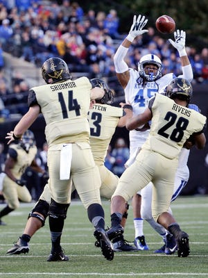 Vanderbilt quarterback Kyle Shurmur (14) passes over the reach of Kentucky linebacker Josh Forrest (45) in the first half of an NCAA college football game Saturday, Nov. 14, 2015, in Nashville, Tenn.