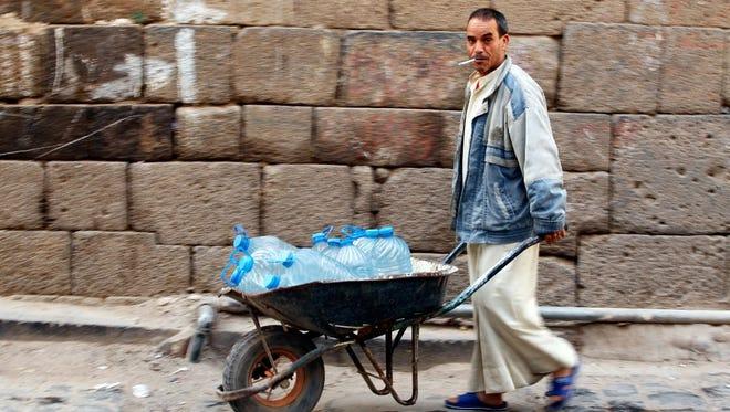 A Yemeni pushes a wheelbarrow with donated bottles of water, Sana, Feb. 10, 2017.
