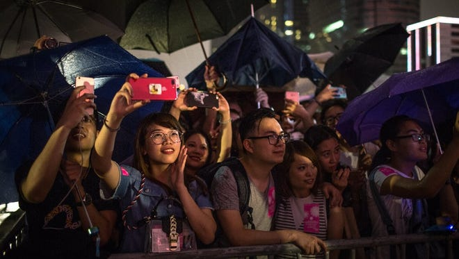 People holding umbrellas under heavy rain at fireworks light up the sky over Victoria Harbour in Hong Kong, China, July 1, 2017. Hong Kong marked the 20th anniversary of the city's handover from British to Chinese rule on July 1