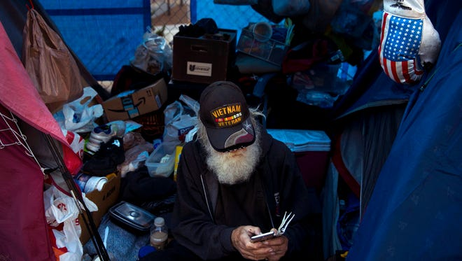 Theodore Neubauer, a 78-year-old Vietnam War veteran, who is homeless, looks at his smartphone while passing time in his tent Friday, Dec. 1, 2017, in Los Angeles.