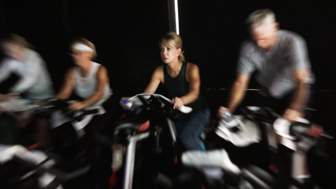 Palm Beach resident Lydia Turner (second from right) works out during a 45-minute spin cycle class at Studios Etc. on March 12. The gym is now offering online classes.