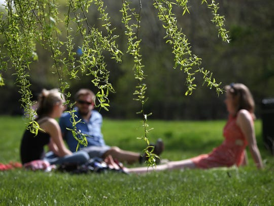 People enjoy a picnic in warmer weather in London, England.