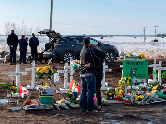 People visit a memorial at the site of a bus crash that killed 16 members of the Humboldt Broncos hockey team.