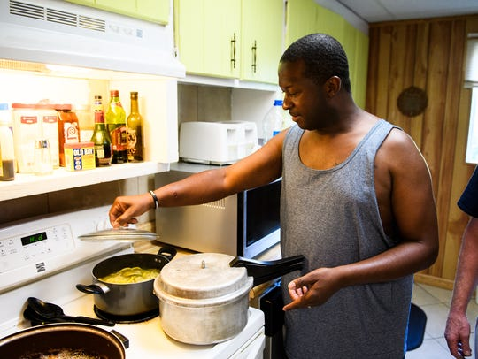 Fred Turner cooks dinner at the Soteria house after