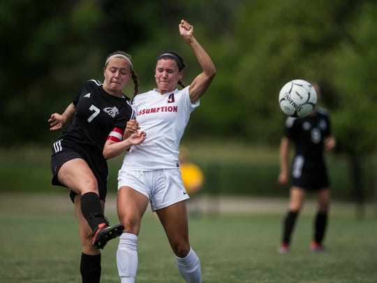 North Polk's Danielle Bonewitz kicks the ball past Assumption's Carly King during the Class 1A girls' state soccer quarterfinal match between Davenport Assumption and North Polk on Thursday, June 7, 2018, at the Cownie Soccer Park in Des Moines.