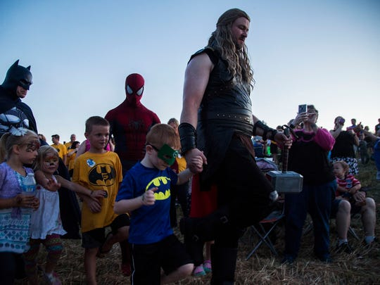 Actors dressed as superheroes are surrounded by children