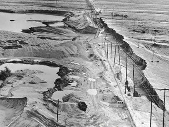 Whitewater River at Indian Avenue as it appeared on March 23, 1965. Indian Avenue was destroyed by floodwaters cutting back from a sand and gravel pit on the downstream side. The closing of Indian Avenue added to the isolation of Palm Springs.