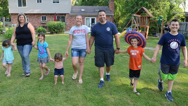 Bethany and Chris Chappell grab hands for a photo at their Milford Township home with Abby, 4, Regina, 6, Jake, 2, McKenzie, 15, Gabe, 8, and Chase, 12.