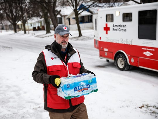 FLINT, MI - JANUARY 21:  American Red Cross volunteer John Lohrstorfer walks down Maryland St. on Flint's north side bringing bottled water and filters to homes on January 21, 2016 in Flint, Michigan.  The Red Cross is supporting state and county efforts to bring water to every household in the city.