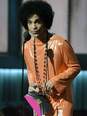 This Feb. 8, 2015, file photo shows Prince as he presents an award on stage at the 57th Annual Grammy Awards in Los Angeles.  Prince died Thursday, April 21, at age 57.
