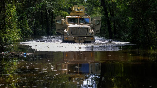 In this U.S. Army National Guard handout, A U.S. Air Force Security Forces Airmen assigned to the South Carolina Air National Guard, 169th Fighter Wing, from McEntire Joint National Guard Base, ride in a Florence County, S.C., Sheriffs Department tactical vehicle to assist law enforcement with evacuation efforts as the Black Creek river begins to crest in Florence, S.C., Sept. 17, 2018.