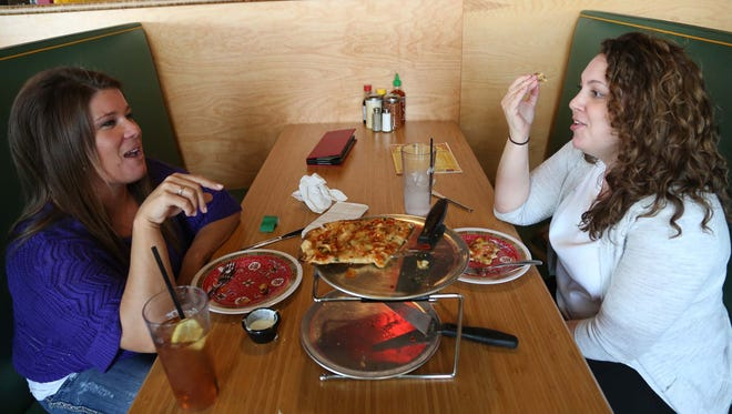 Juliana Walton, 34 of Altoona and Jessica Dube, 29 of Minneapolis, MN, eat crab rangoon and bacon popper pizza on opening day at Fong's in Ankeny on Tuesday, April 28, 2015. The chinese themed pizza place is located at 1450 S. W. Vintage Parkway, Suite 120 in Ankeny.