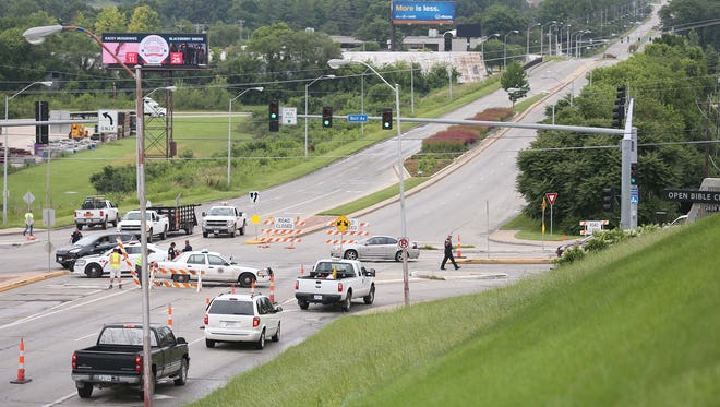 Des Moines police officers direct traffic as city workers place orange cones and road closed signs up at the intersection of Fleur Drive and Bell Avenue on Thursday, June 25, 2015, in Des Moines. Fleur was closed between MLK and Bell due to rising river levels.