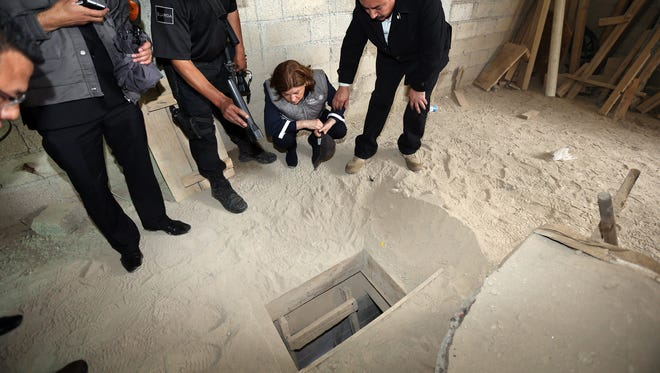 """Handout photo released by the Attorney General of Mexico showing Mexico's Attorney General, Arely Gomez, looking at the alleged end of the tunnel through which Mexican drug lord Joaquin """"El Chapo"""" Guzman could have escaped from the Altiplano prison."""