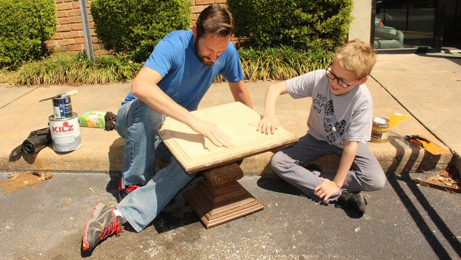 Michael Capilouto gets a helping hand from son Garvyn as the two sandpaper a small piece of furniture outside the Family Sunshine Center as part of Temple Beth Or's day of volunteerism. Alvin Benn/Special to the Advertiser.