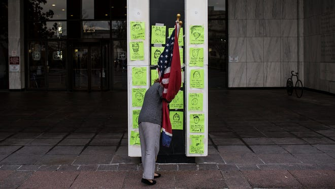 Cary Miller tapes her 'mugshot' to the outside of Memphis City Hall during a protest Tuesday of the 'blacklist' of 81 people that require a police escort in City Hall.