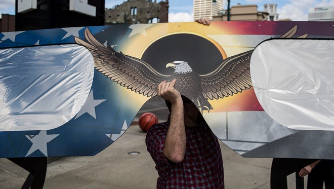 Brian Brock,a graphic designer for American Paper Optics, helps set up a giant pair of solar eclipse glasses outside of the FedExForum in Downtown Memphis as part of the company's marketing campaign to sell glasses for the Aug. 21 total eclipse that will slice across the United States.