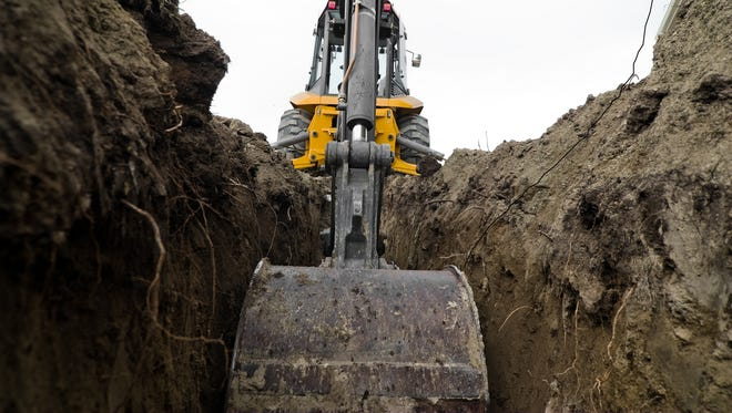 A backhoe digging a trench for some electrical/plumbing lines.