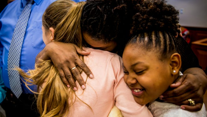 Christina Sanders embraces her newly adopted daughter Cayley, 12, and her biological daughter, Caitlyn, 9, after the Sanders family adoption of Cayley and her five siblings was finalized in Hamilton County Probate Court Thursday, April 27, 2017. The couple have five biological children and now have a total of eleven children.