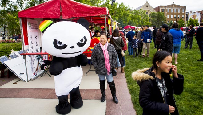 A panda character waits to pose for photos with the crowd at The Asian Food Fest at Washington Park Saturday, May 14, 2016.