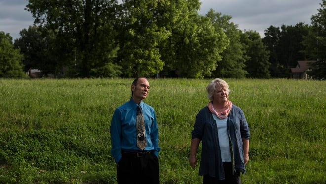 Vaughan Dewar, an opponent, and Pat Brown, a supporter, of the Overton Gateway apartments stand near where the apartments are proposed to be built. The apartments would be built on vacant land near the intersection of Sam Cooper Boulevard and East Parkway.