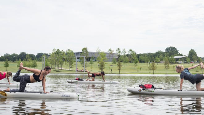 July 15, 2017 - Class participants get into a pose on top of their stand up paddle boards during a stand up paddle board yoga class on Hyde Lake at Shelby Farms park.