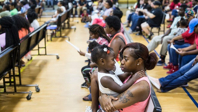 Johneisha Sanford holds her daughter, Jordyn Sanford, 2, during a orientation for parents at one of Willie Herenton's charter schools in July 2017.