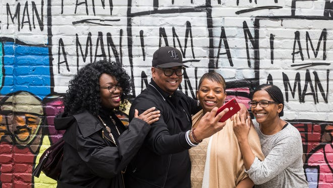 "From left, Dr. Tiffany Tyler, Dr. Malcolm Gillard, Angella Chalk and Charlotte Morgan take a selfie in front of the ""I am a Man"" mural along South Main Street near the National Civil Rights Museum on March 29, 2018."