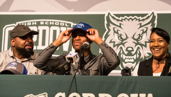 April 13, 2018 - Cordova point guard Tyler Harris, center, puts on a University of Memphis hat while announcing that he was signing a national letter of intent with the Tigers.