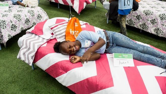 "April 28, 2018 - Aakia Patrick, 10, smiles as she lays on her new bed that she received during the Ashley HomeStore and the Memphis Tigers ""Hope to Dream"" event at the Billy J Murphy Athletic Complex. ""I think it's great,"" she said while talking about her new bed. 100 children received an entire bed set at the event."