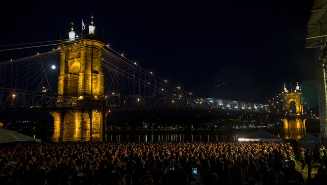 A full moon rises over the John A. Roebling Suspension Bridge, while The National performs at Homecoming Festival on the west stage at Smale Riverfront Park Sunday, April 29, 2018.
