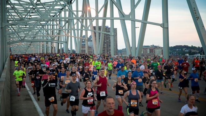 Runners cross the Taylor Southgate Bridge after the one mile marker at the 20th annual Flying Pig Marathon Sunday, May 6, 2018.