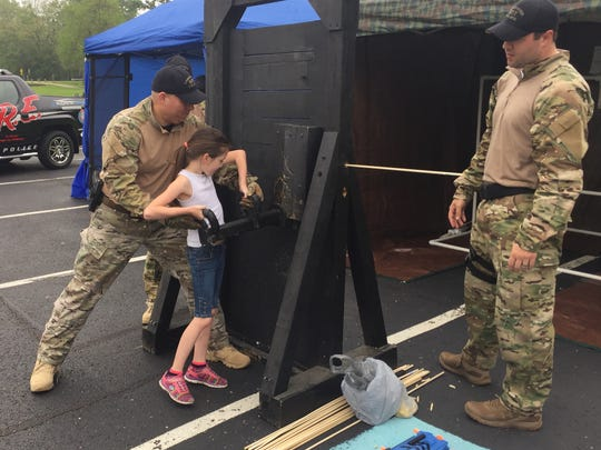 Sgt. Matt Ream of the city's Special Response Team shows Sydney Barton, 8, how to break through a door Saturday at the Lancaster Citizen Police Academy Alumni Association Kids And Cops Day at Ohio University Lancaster.