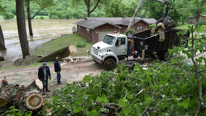 Baxter County employees work to remove a large Cottonwood Tree from Riverview Drive Monday in Norfork as the muddy river rushes by. Several inches of rain fell over the weekend, causing widespread damage to Twin Lakes Area roadways.