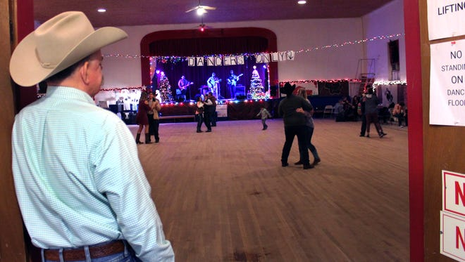 Phil Rockett leans against the door frame leading into a gym turned into a dance hall in Oplin. The Rockett family has taken over running the weekend dance, continuing a tradition that goes back more than 40 years.