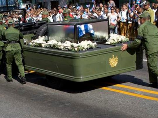 Soldiers push the jeep and trailer carrying the ashes of the late Fidel Castro after the jeep briefly stopped working during Castro's funeral procession near Moncada Fort in Santiago, Cuba, Saturday, Dec. 3, 2016. Castro's ashes will be interred Sunday in Santiago, ending a nine-day period of mourning that saw Cuba fall silent as thousands paid tribute to photographs of Castro and sign oaths of loyalty to his socialist, single-party system.