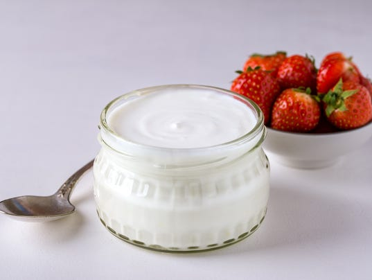 White yogurt in glass bowl with spoon and starwberries on white background.