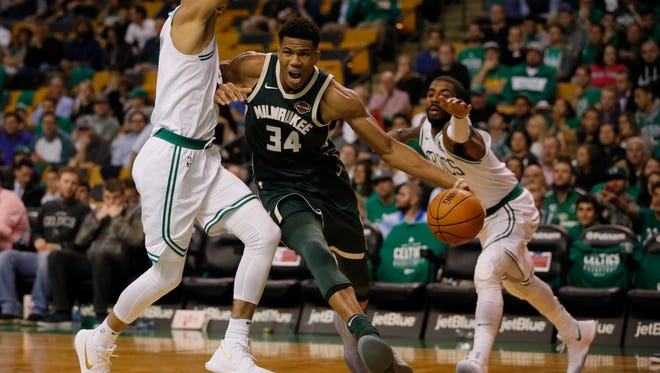 Giannis Antetokounmpo drives the ball against the Celtics' Jayson Tatum (left) and Kyrie Irving (11) in the third quarter.